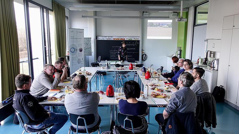 Die Teilnehmer*innen sitzen zusammen an einem Tisch vor einer Tafel und unterhalten sich.an einem